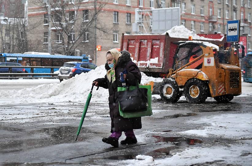 Женщина идет по улице во время уборки снега