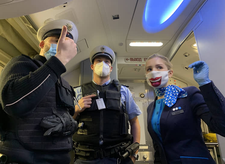 Стюардесса и сотрудники полиции у входа в самолет