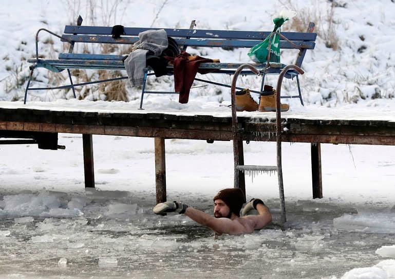 Ломянки, Польша. Мужчина купается в озере при температуре минус 12 градусов по Цельсию