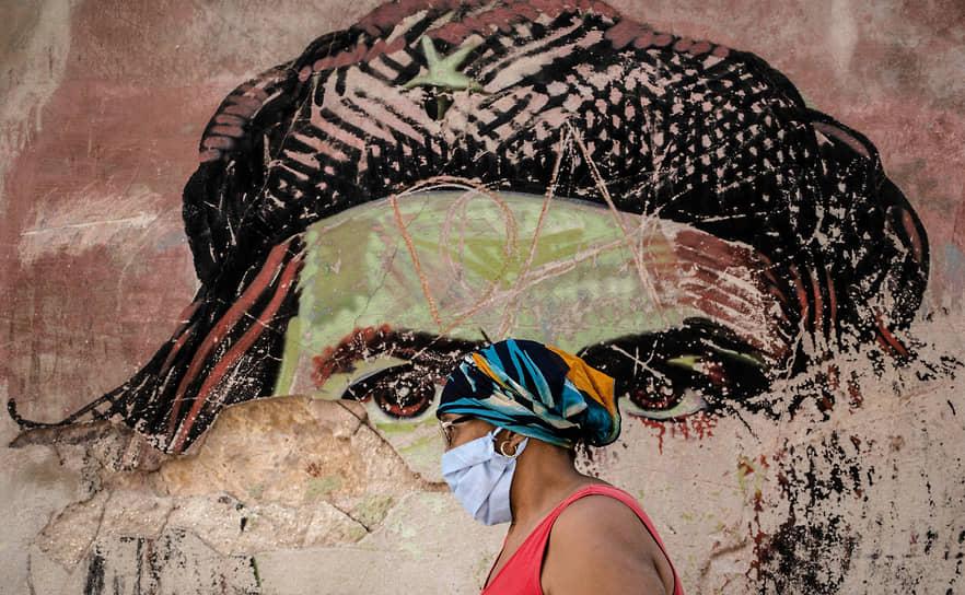 Гавана, Куба. Женщина в медицинской маске идет мимо полуразрушенного граффити с портретом Эрнесто Че Гевары