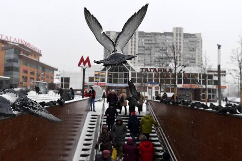 Москва, Россия. Голубь пролетает над входом станции метро «Марксистская»