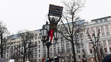 Мужчина с плакатом против Алексея Навального на фонарном столбе