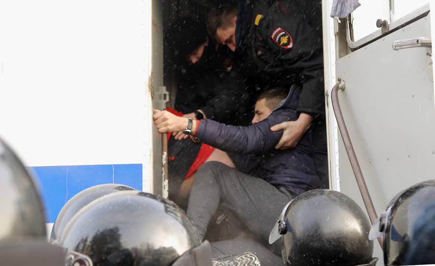 Сотрудники полиции во время задержания и посадки в автозак участника митинга в Новосибирске