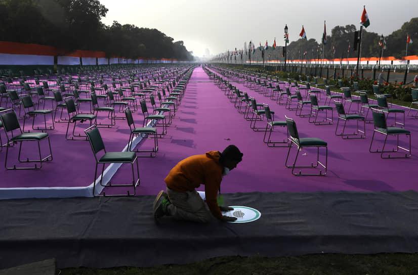 Нью-Дели, Индия. Рабочий накануне празднования Дня республики наклеивает объявление о необходимости ношения маски