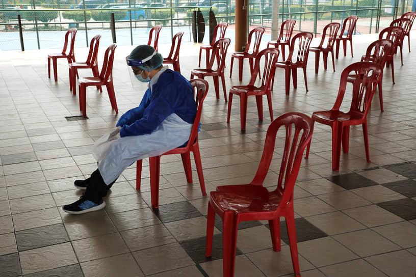 Петалинг-Джая, Малайзия. Медработник отдыхает в центре тестирования на COVID-19