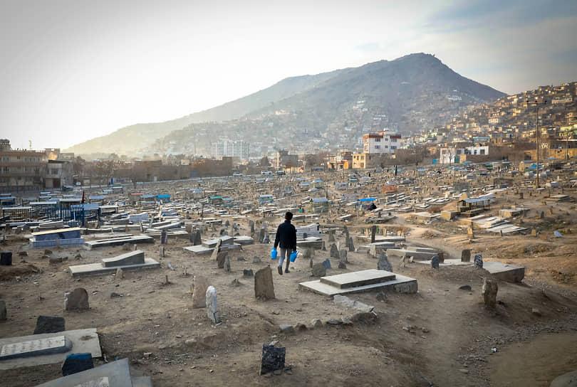 Кабул, Афганистан. Продавец воды идет через кладбище в поиске покупателей