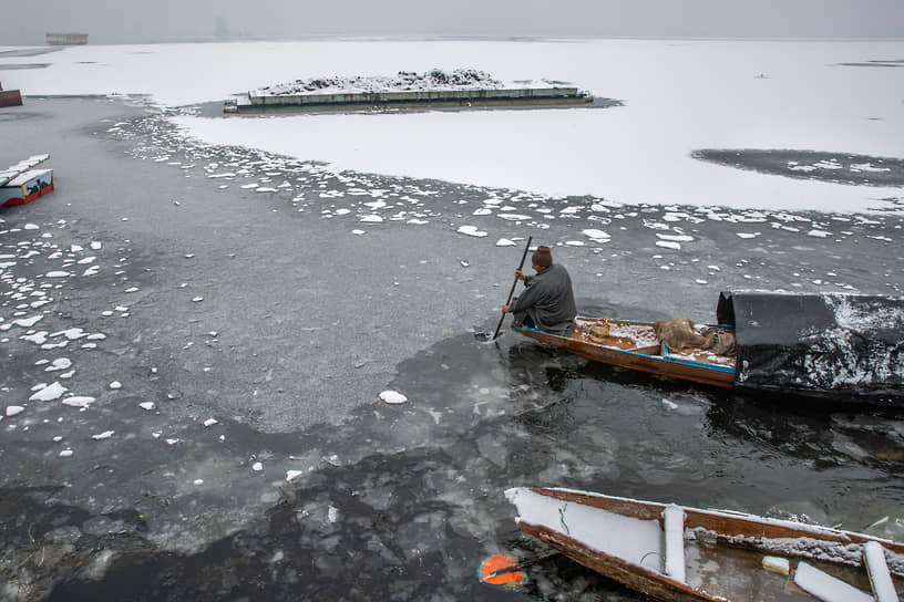 Шринагар, Индия. Мужчина плывет на лодке по замерзшему озеру