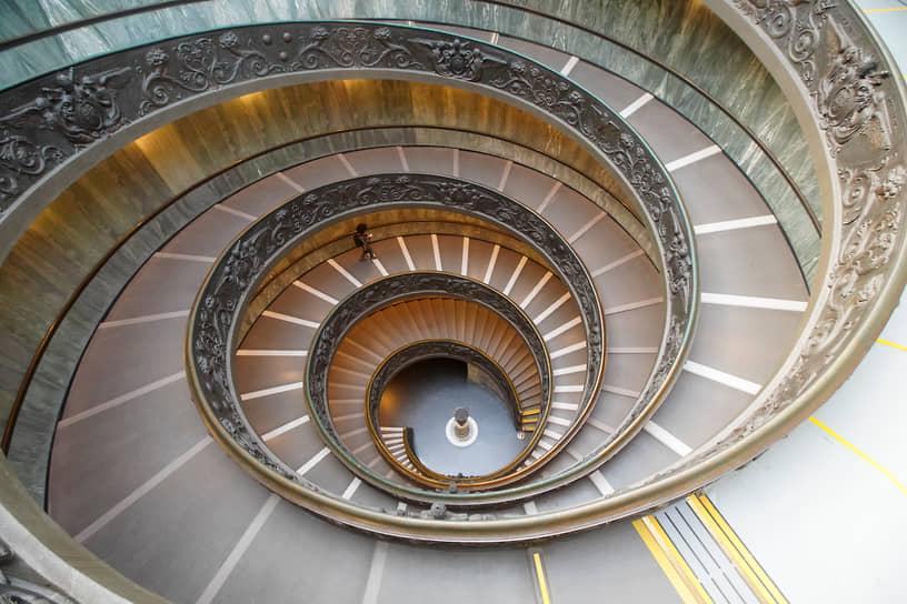 Ватикан. Посетитель музея идет по лестнице, спроектированной архитектором Джузеппе Момо