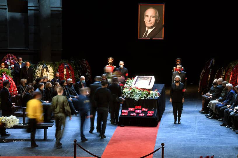 Пришедшие проститься проходили через главный вход и поднимались на сцену. В центре стоял закрытый гроб, перед ним — государственные награды