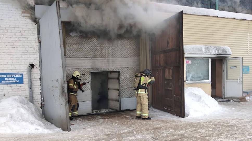Пожарные во время тушения пожара на складе, у них на спине — дыхательные аппараты-однобаллонники