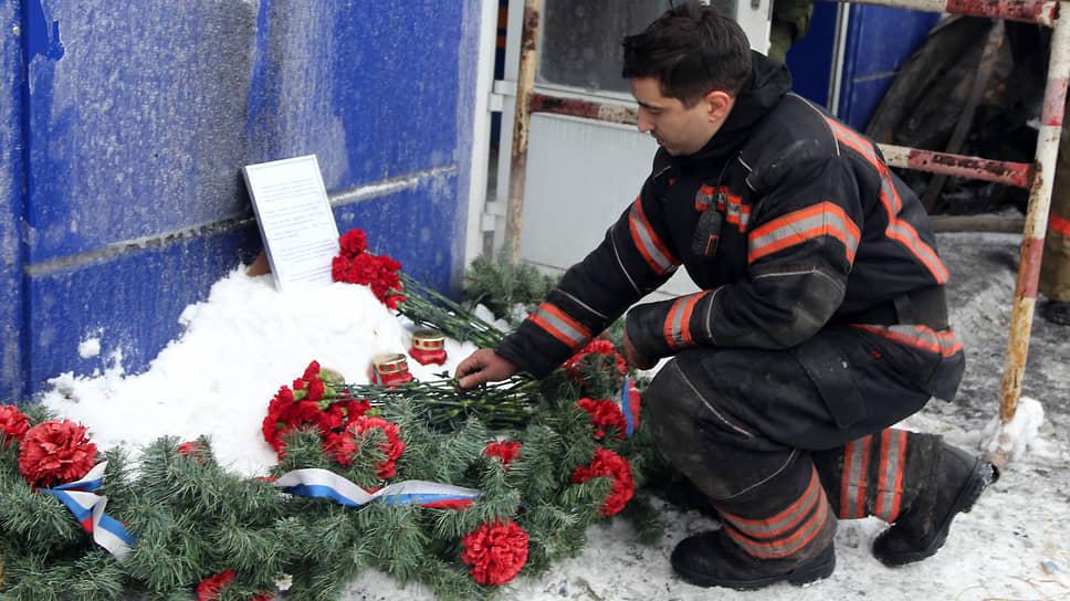 Сотрудник МЧС возлагает цветы к стенам склада, где погиб его коллега