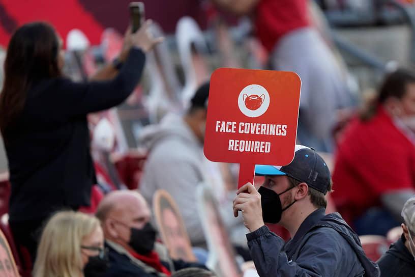 Работник стадиона следит за соблюдением масочного режима