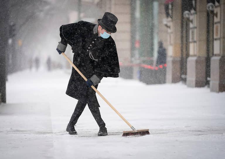 Берлин, Германия. Работник отеля чистит тротуар