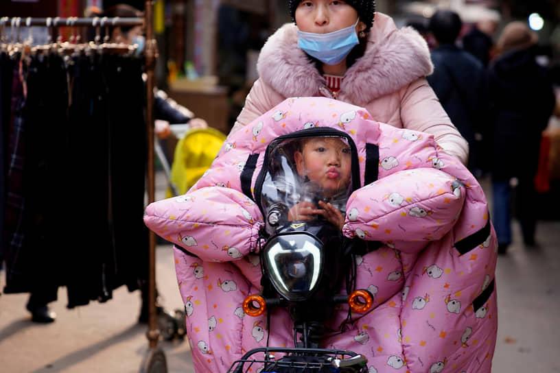 Ухань, Китай. Женщина едет с ребенком на велосипеде
