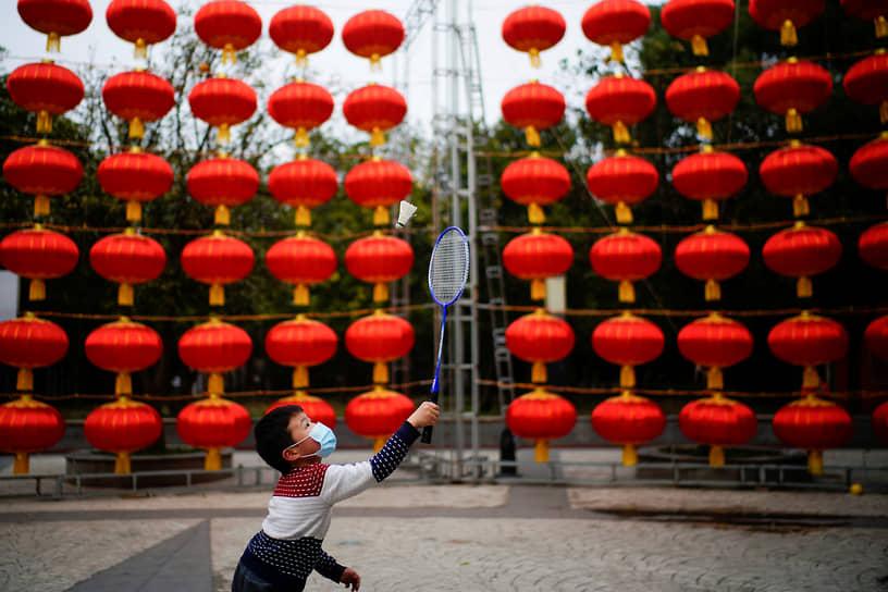 Ухань, Китай. Мальчик играет в бадминтон на фоне уличных украшений к китайскому Новому году