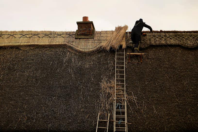 Голуэй, Ирландия. Мужчина ремонтирует крышу старого дома