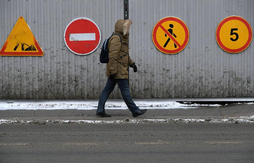 Москва, Россия. Прохожий на фоне дорожных знаков