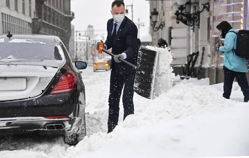 Москва. Мужчина в деловом костюме убирает снег с дороги