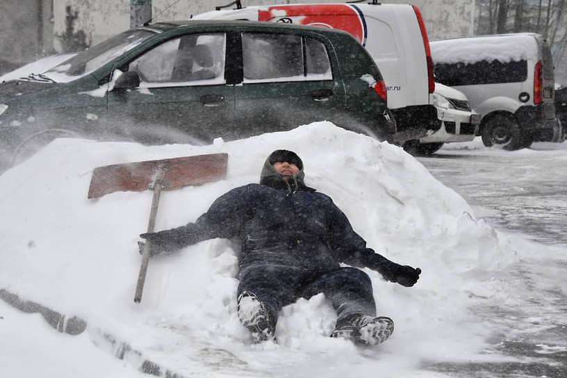 Сотрудник коммунальной службы города отдыхает на снежном сугробе после уборки снега