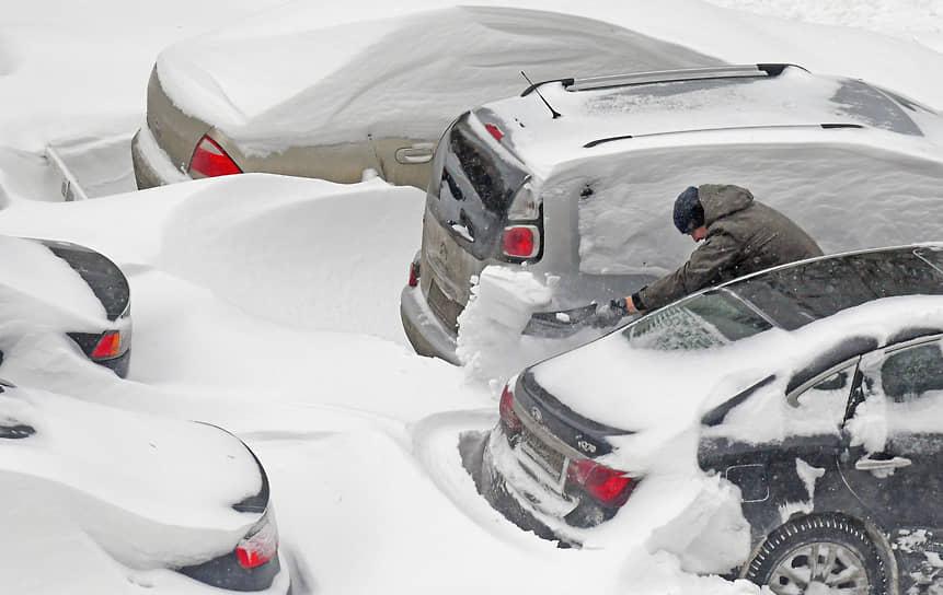 Водитель чистит автомобиль от снега