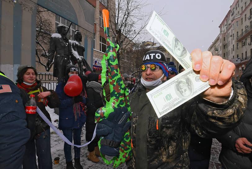 На акцию пришли активисты «Национально-освободительного движения» (НОД). Они были одеты в шуточные костюмы и каски солдат НАТО, держали в руках надувные автоматы и пытались раздавать участницам сувенирные «доллары». В ответ активистки кричали: «Позор!»