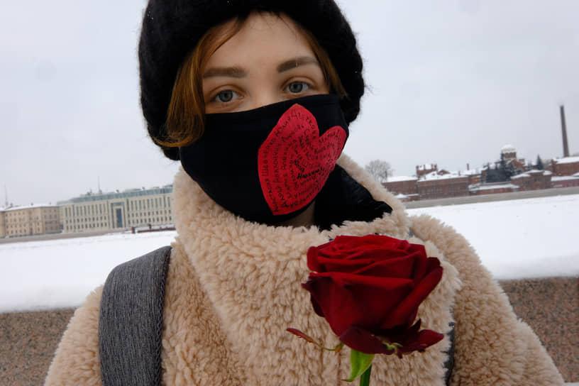 Девушка с розой у памятника жертвам политических репрессий на Воскресенской набережной в Санкт-Петербурге