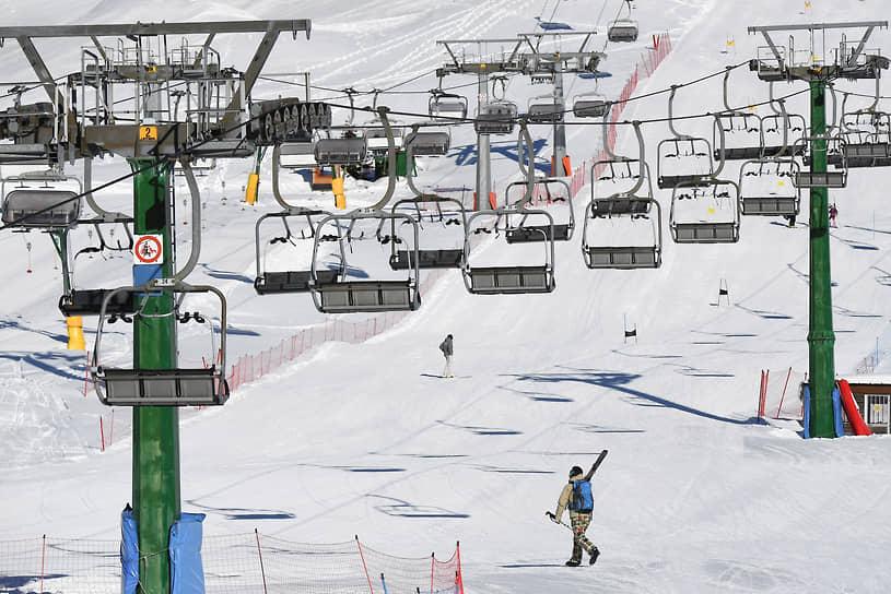 Понте-ди-Леньо, Франция. Турист с лыжами поднимается на холм пешком, так как подъемники не работают из-за закрытия горнолыжных курортов на время пандемии коронавируса