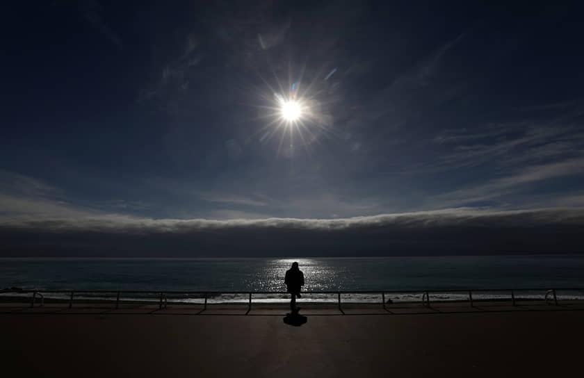 Ницца, Франция. Местный житель сидит в одиночестве на Английской набережной