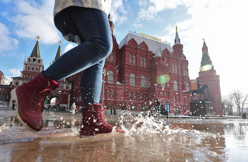 26 февраля. Москва. Девушка идет по луже на Манежной площади