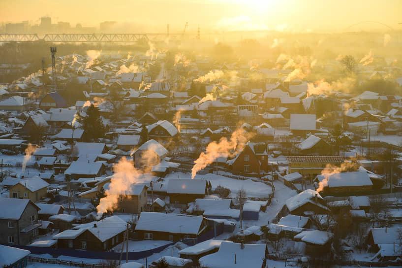 8 февраля. Новосибирск. Дымящиеся на морозе трубы домов частного сектора на рассвете