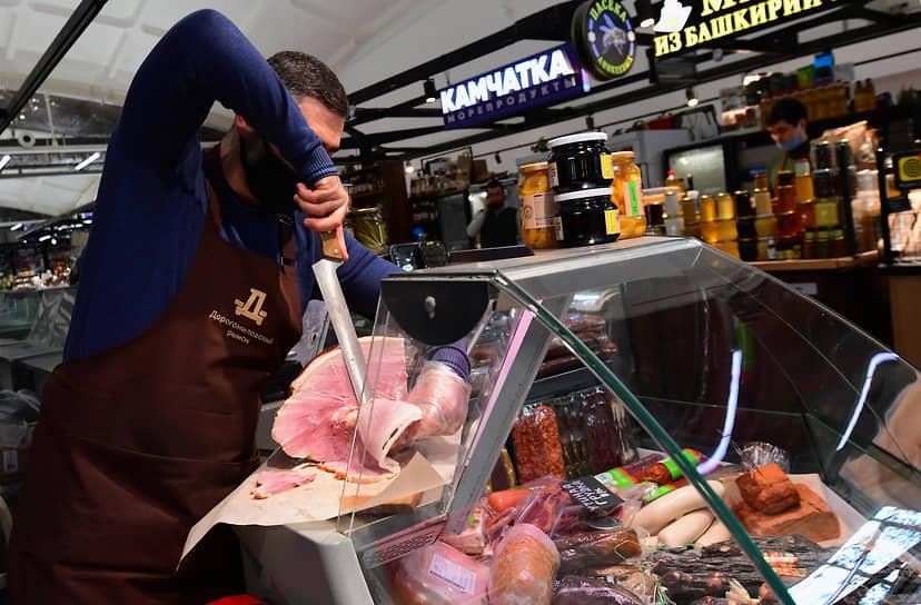 Москва, Россия. Продавец нарезает мясо на Дорогомиловском рынке