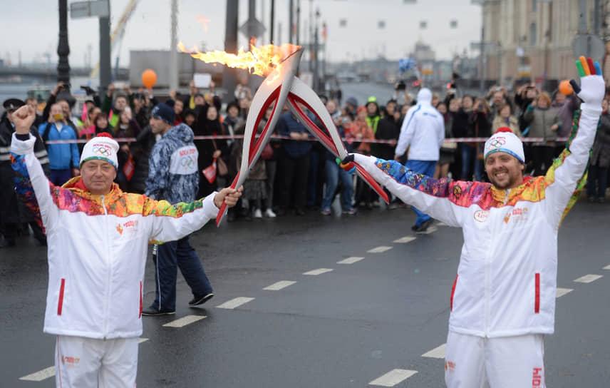 Алексей Мишин (слева) во время эстафеты Олимпийского огня в Санкт-Петербурге 27 октября 2013 года