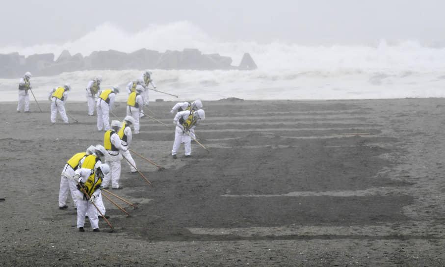 Пляжи возле «Фукусимы» были завалены радиоактивным мусором. Непосредственно от радиации во время аварии никто не погиб, но, по словам ученых, около 1,8 тыс. человек подвержены высокому риску заболевания раком из-за облучения<br> На фото: поиск останков жертв землетрясения и цунами 2011 года