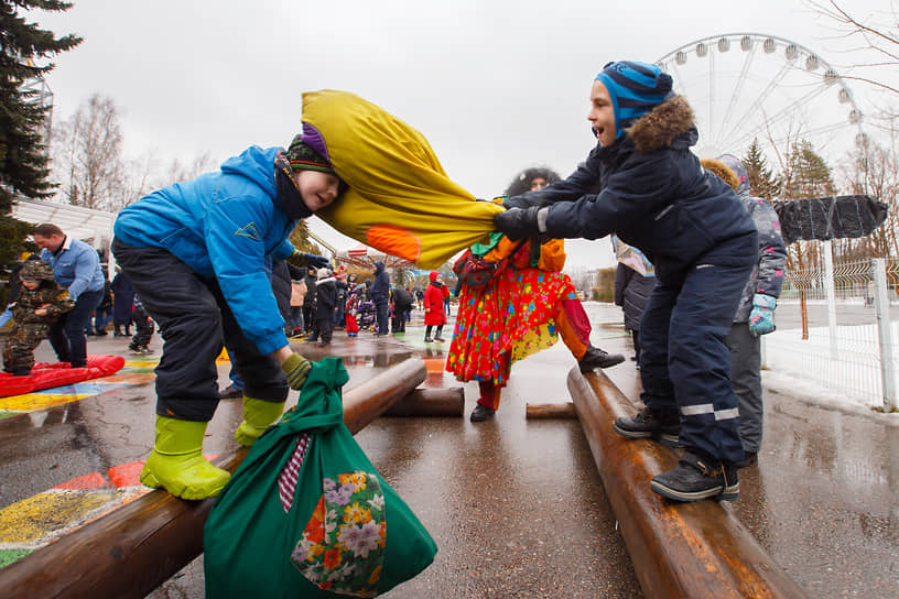 Дети во время традиционной масленичной забавы в парке аттракционов