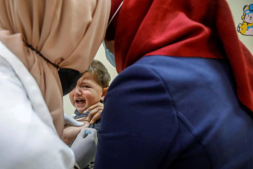 Тубас, Палестина. Медработник делает прививку ребенку
