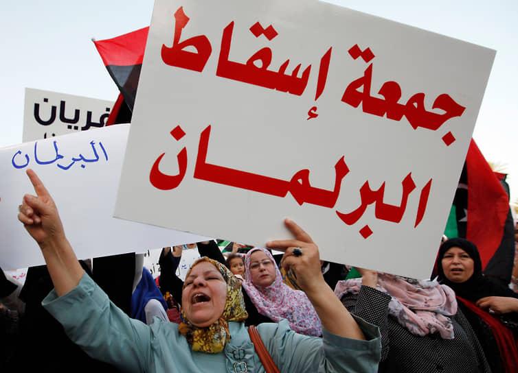 В августе 2014 года ВНК официально передал власть Палате представителей, сформированной по результатам выборов, но часть членов ВНК отказалась передавать власть и создала Новый всеобщий национальный конгресс. В стране оформилось двоевластие с Палатой представителей, заседающей на востоке — в Тобруке, и НВНК на западе — в Триполи<br> На фото: митинг в Триполи против Палаты представителей
