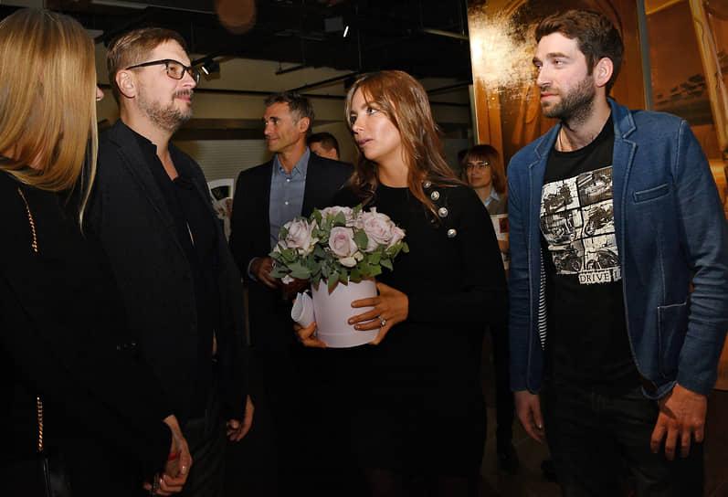 Владелица галереи ILONA-K artspace Илона Кесаева (в центре) и художник Арсений Власов (справа) на церемонии открытия выставки «Следуя мечте»