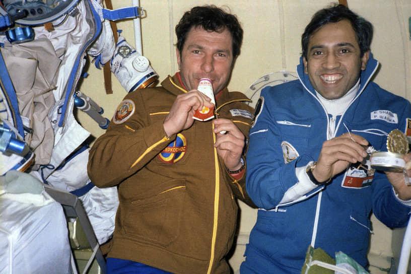 <b>Ракеш Шарма, Индия (справа)</b><br> Совершил полет 3 апреля 1984 года в качестве космонавта-исследователя в состав экипажа корабля «Союз Т-11». На космической станции «Салют-7» провел ряд медицинских экспериментов, в том числе по применению йоги для поддержания здоровья космонавтов во время длительных полетов. Во время полета провел сеанс связи с премьер-министром Индии Индирой Ганди и сказал, что Индия выглядит «лучше всех в мире». Впоследствии работал летчиком-испытателем, принимал участие в работах по созданию индийского легкого истребителя
