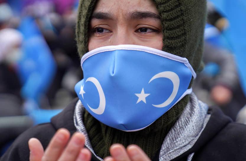 Стамбул, Турция. Мужчина в маске с флагом Восточного Туркестана протестует против визита в страну главы МИД Китая Ван И