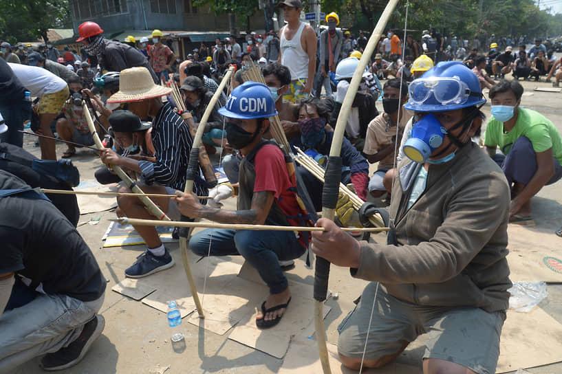Протестующие с луками и стрелами готовятся противостоять полиции в Янгоне