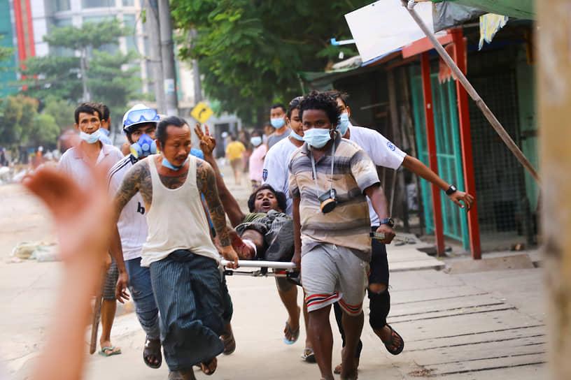 Протестующие переносят на носилках раненого во время демонстрации в Янгоне