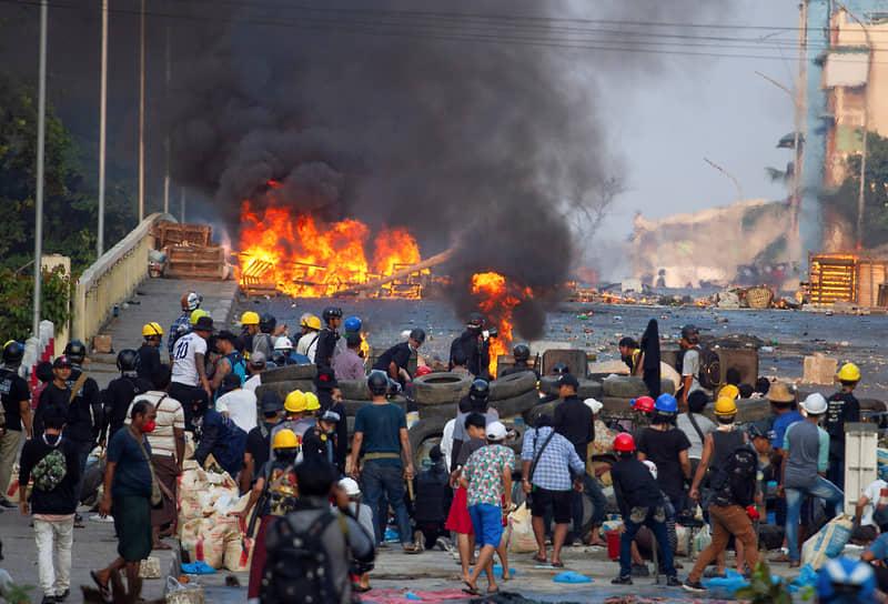 Протестующие у баррикады во время столкновения с полицейскими в Янгоне