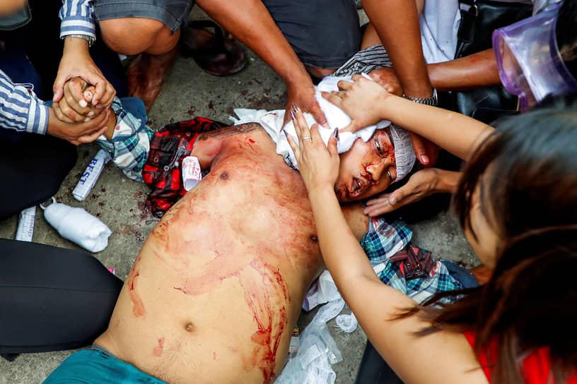 Раненому во время протестов пытаются оказать первую помощь