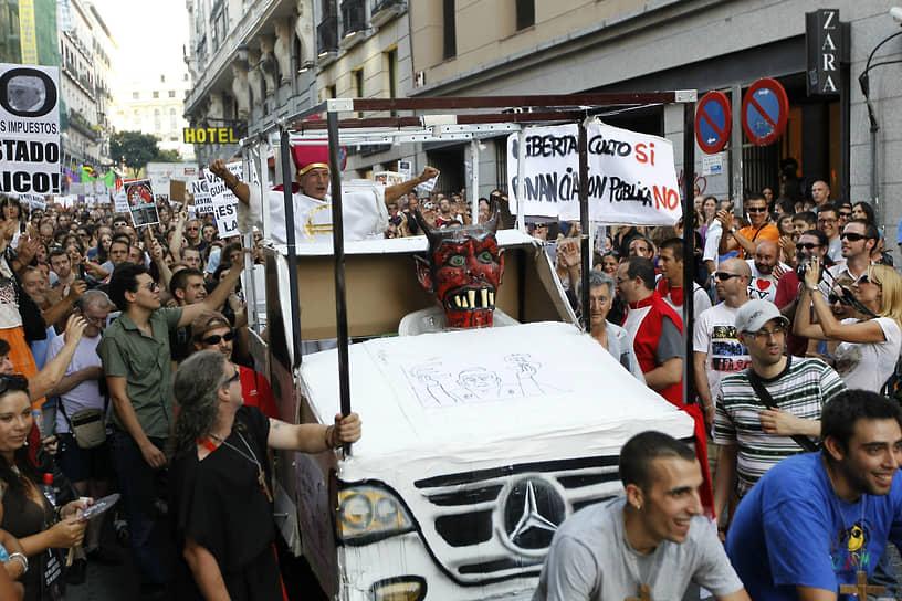 В августе 2011 года жители Мадрида протестовали из-за визита папы римского Бенедикта XVI. Он приехал в столицу Испании на празднование Всемирного дня молодежи. Манифестанты выступали против вмешательства церкви во внутренние дела страны и за сокращение расходов на мероприятия. В столкновениях с полицией более 10 человек получили ранения