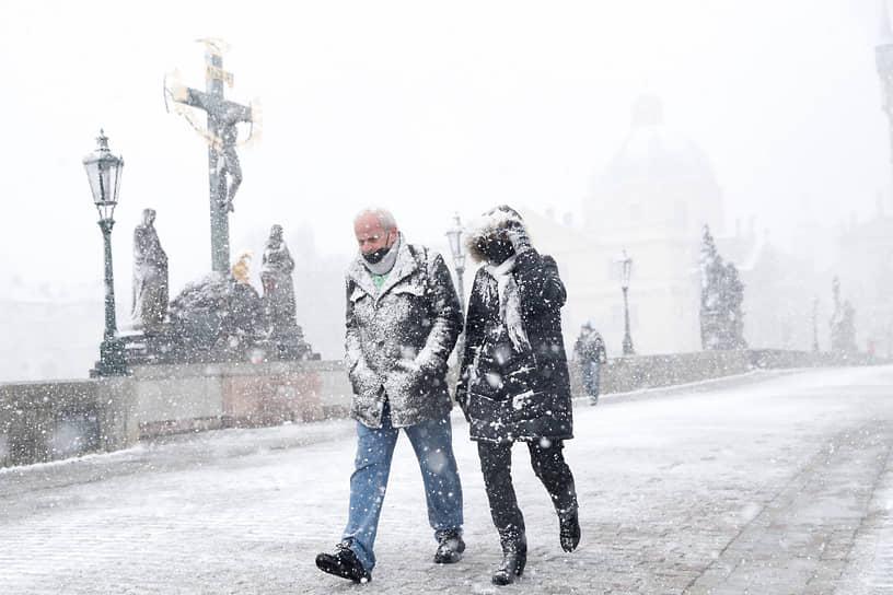 Прага, Чехия. Люди в снегу идут по Карлову мосту