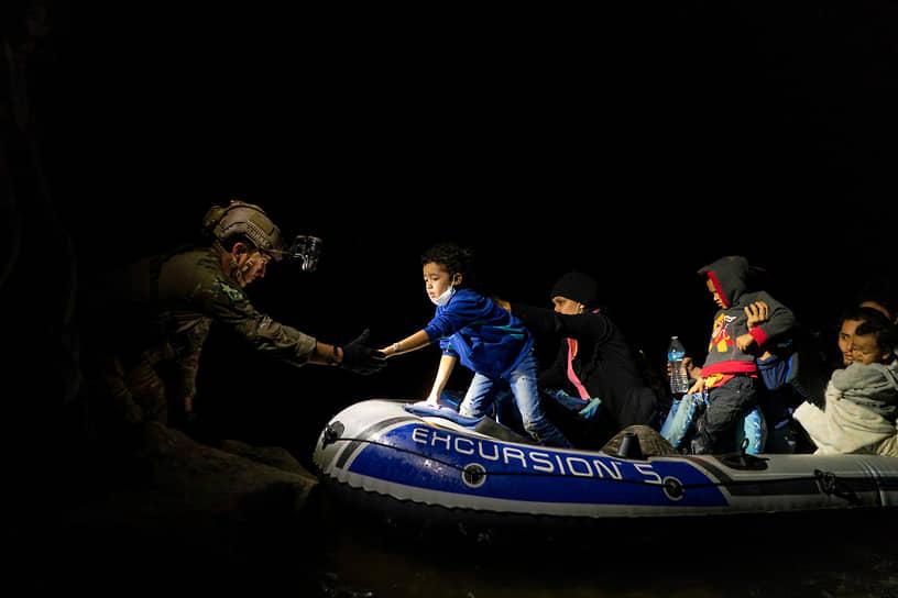 Рома, штат Техас, США. Рейнджер помогает сойти на берег семье беженцев, переплывших на надувной лодке реку Рио Гранде на границе с Мексикой