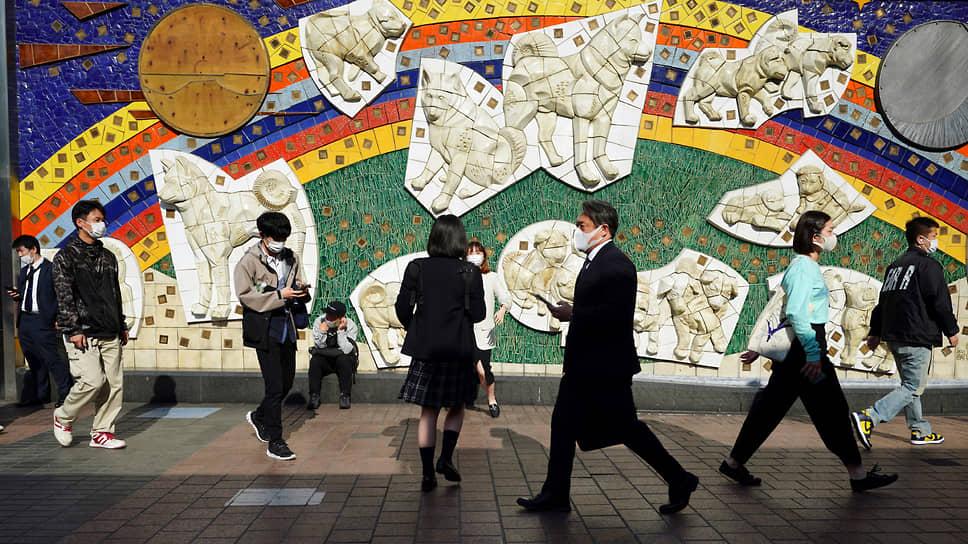 Токио, Япония. Местные жители в защитных масках прогуливаются