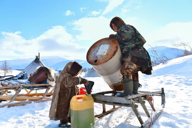 Мужчина переливает бензин из бака в канистру для заправки снегохода