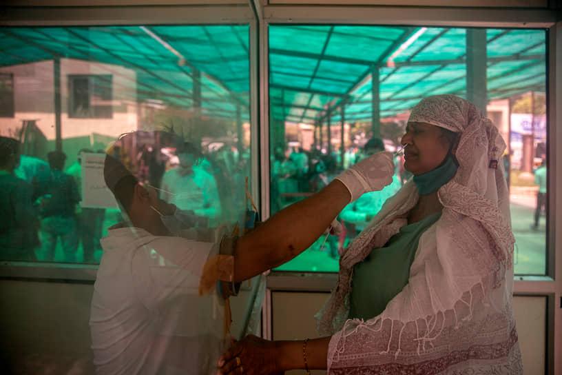 Нью-Дели, Индия. Медработник берет мазок на коронавирус