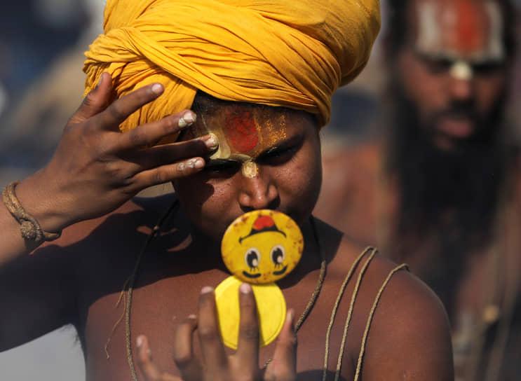 Хардвар, Индия. Индуистский аскет смотрит в зеркало перед утренней молитвой на берегу реки Ганг